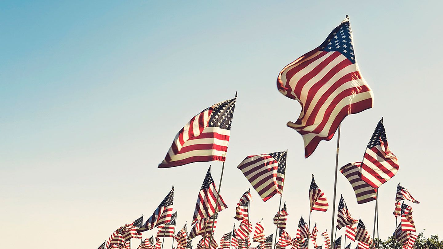 Over 100 United States flags are raised in the air with a handful of other country flags lost in the background.