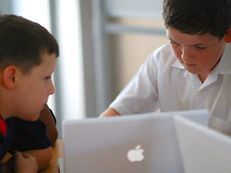 Two young boys are sitting next to each other in class with laptops in front of them.