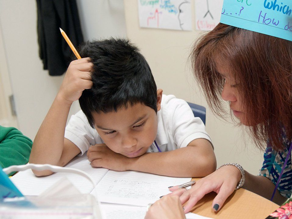 A young boy is sitting at his desk beside his teacher. His left forearm is on his desk, his head resting against it. His right elbow is resting on his desk with his hand against his head. He's looking at his open notebook, working with his teacher.