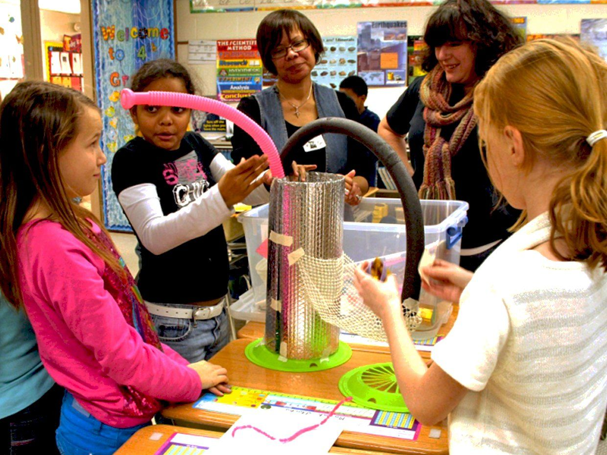 Three elementary-aged girls and two female teachers are standing around three rectangular desks pushed together with a student-made contraption standing on the center desk. The contraption is a large, circular, aluminum-looking tube standing about two to