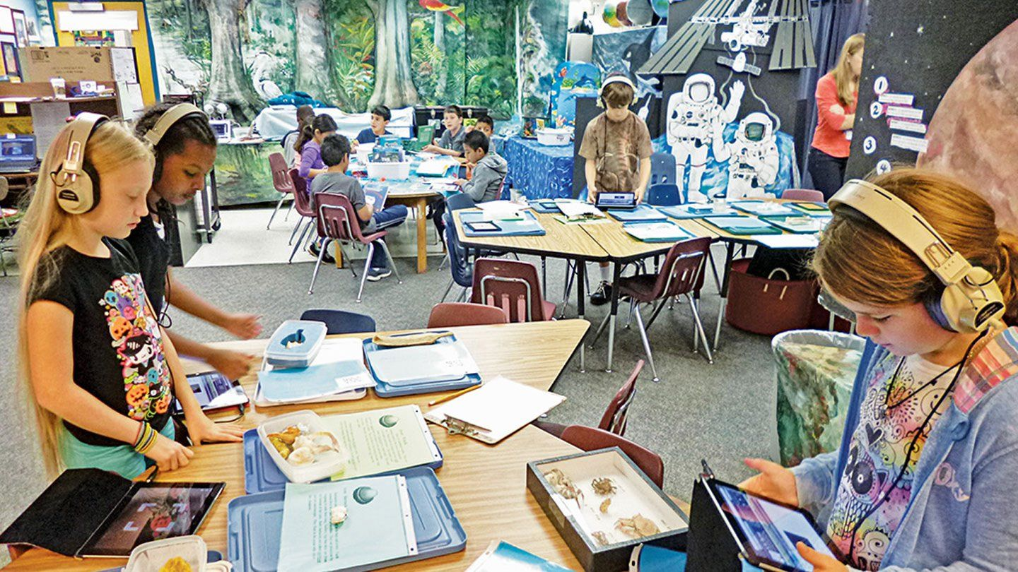 Tablets and lamented information sheets next to boxes filled with marine life span across nine classroom tables. Seven students are sitting at one table, two students are standing together, and two others wearing headphones are working individually.