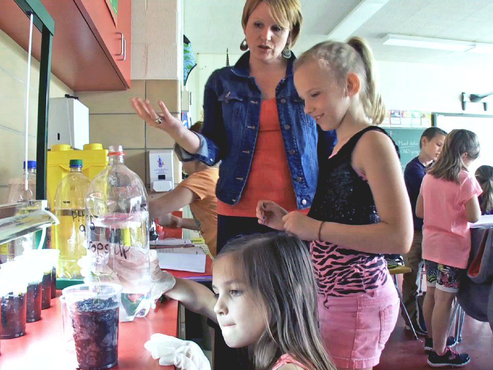 Teacher standing talking with a student as they watch a girl pouring liquid into cups at a counter