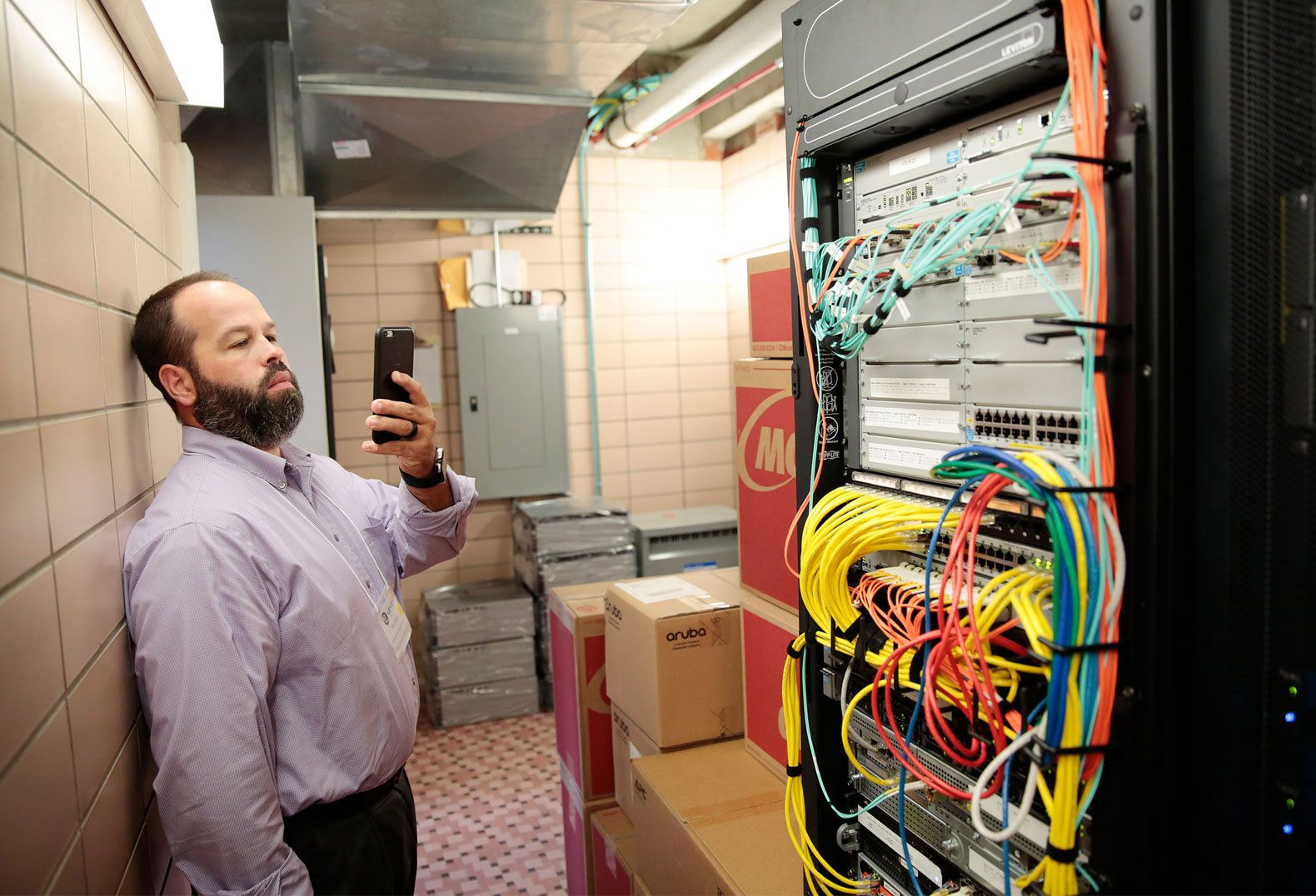Mike Wielgus, an IT teacher from Troy, Illinois, photographs a server room during a technology tour of West Leyden High School.