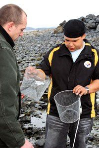 Jordan Geffe sets crab traps with teacher Jed Palmer for a science experiment.
