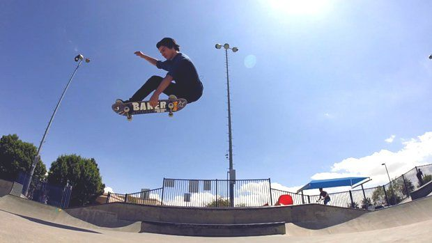 A skateboarder catches some air in a skate park.
