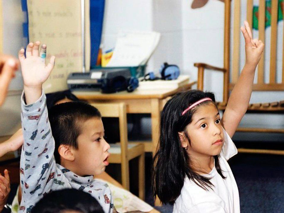 A closeup of two young students sitting on the classroom floor, raising their hands.