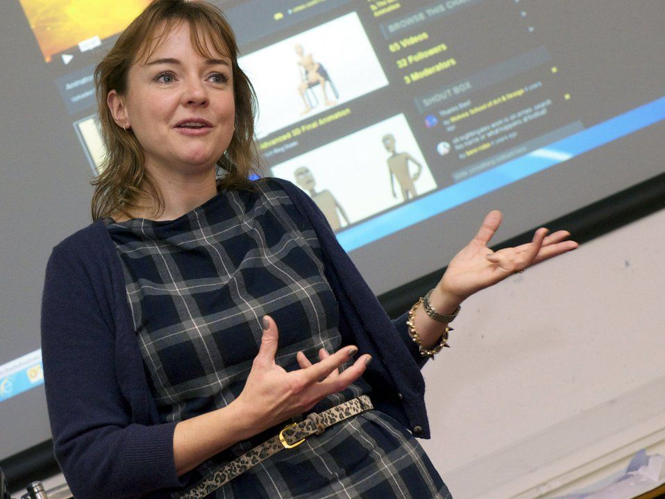 A closeup of a female teacher standing in front of a projector. It looks as if she's addressing her class, speaking, with her hands out, gesturing.