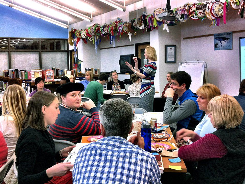 A group of adults are sitting among four tables, six to a table, in a library. Paper plates, popcorn bags, soda, and water bottles are on top of their tables, alongside open binders. A female adult is standing in front of everyone, addressing them.
