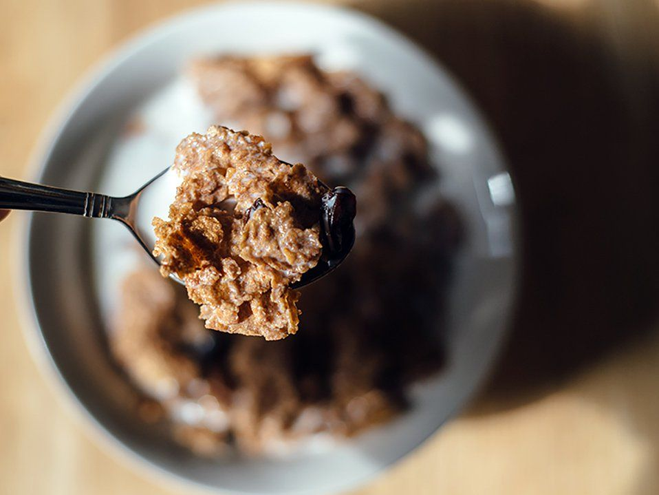 A closeup of a spoon with milk, corn flakes, and raisins. The rest of the image is out of focus. Beneath the spoon is a bowl filled with cereal on a light brown, wooden table.