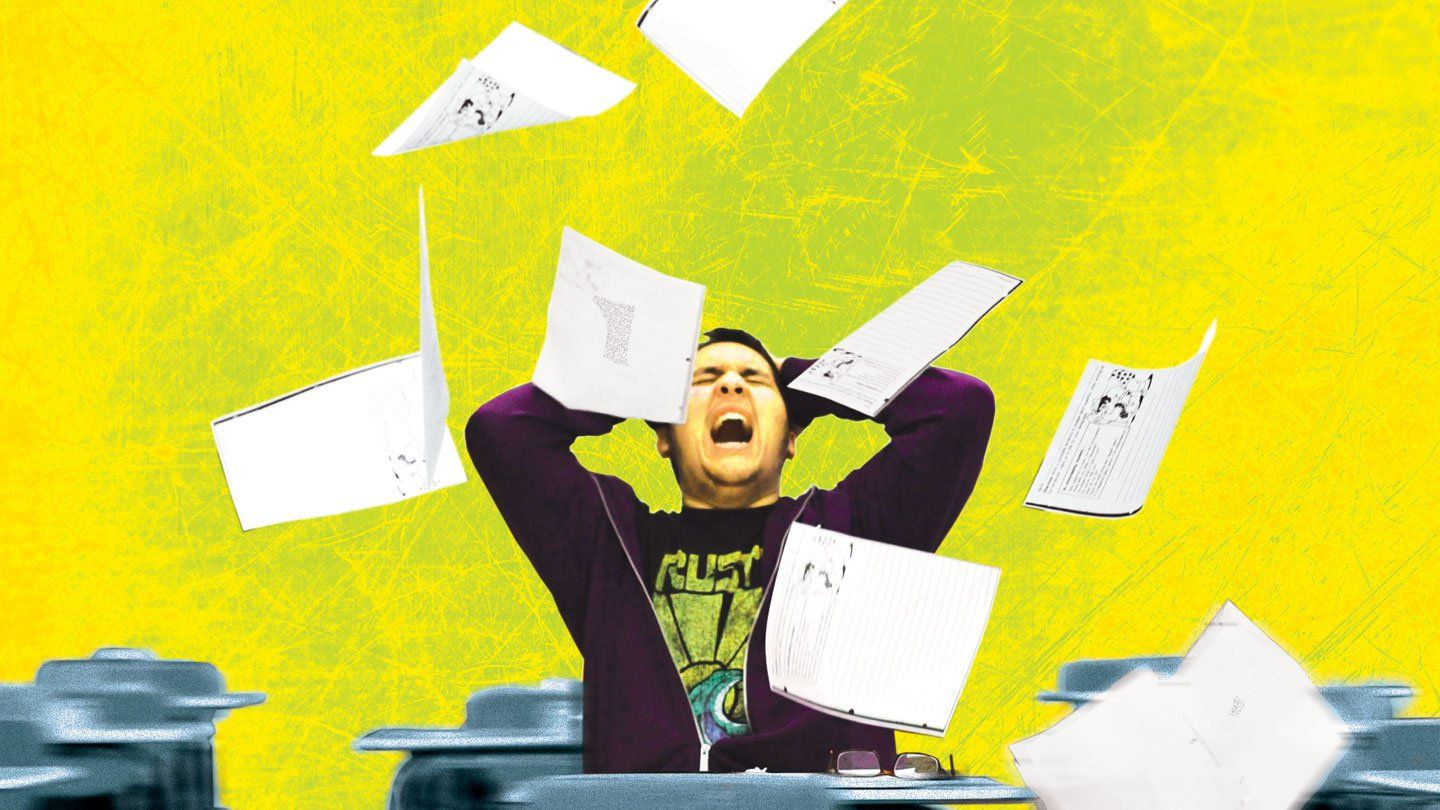 A teenage boy is sitting in a classroom by himself. His hands are on his head, his head is tilted back, his eyes are closed, and he's yelling. A handful of papers are up in the air around him, falling down.