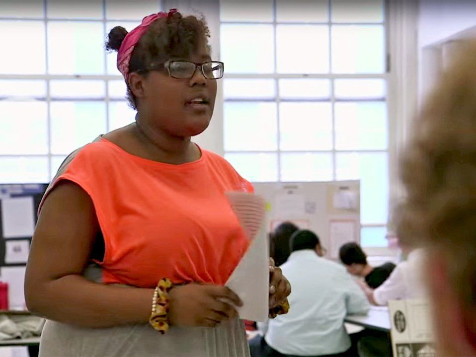 A teenage girl is standing in a classroom, holding a piece of paper, speaking to a small group of people, while other students are grouped throughout the classroom.