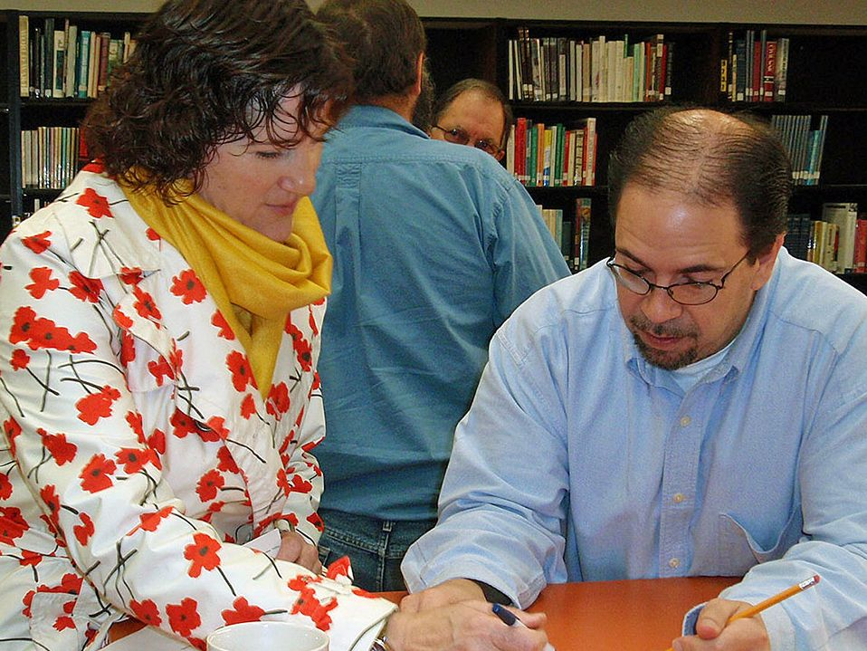 A woman in a floral sweater and a yellow scarf is standing, pointing to a piece of a paper on a table with her pen, and a man wearing glasses and a blue button-up shirt is sitting beside her, looking at the same paper. A bookshelf is behind them.