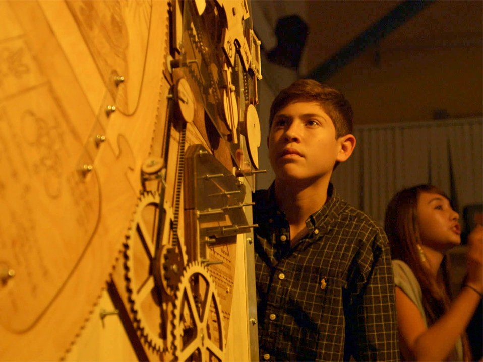 A young teenage boy is standing next to and staring at a huge assembly of clock gears.