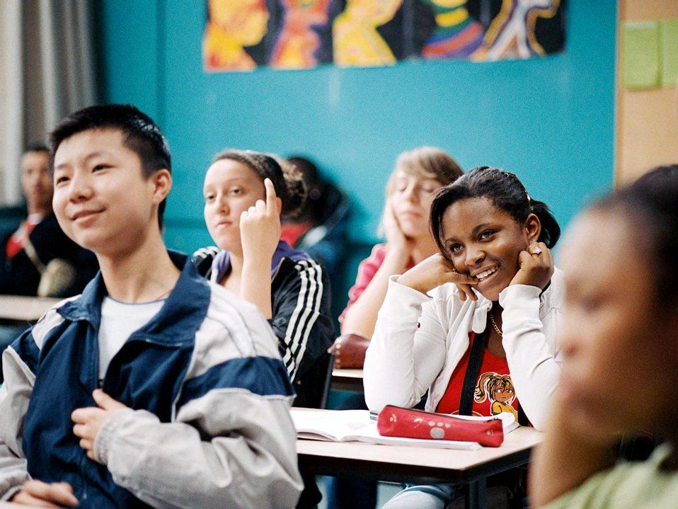 A group of high school students are sitting at desks in class, all looking towards the front, smiling.