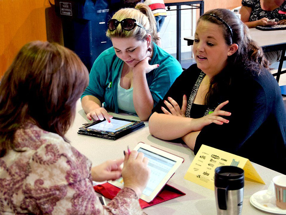 Three female teachers are sitting at a table, two on one side and one on the other, talking to each other and looking at their tablets.
