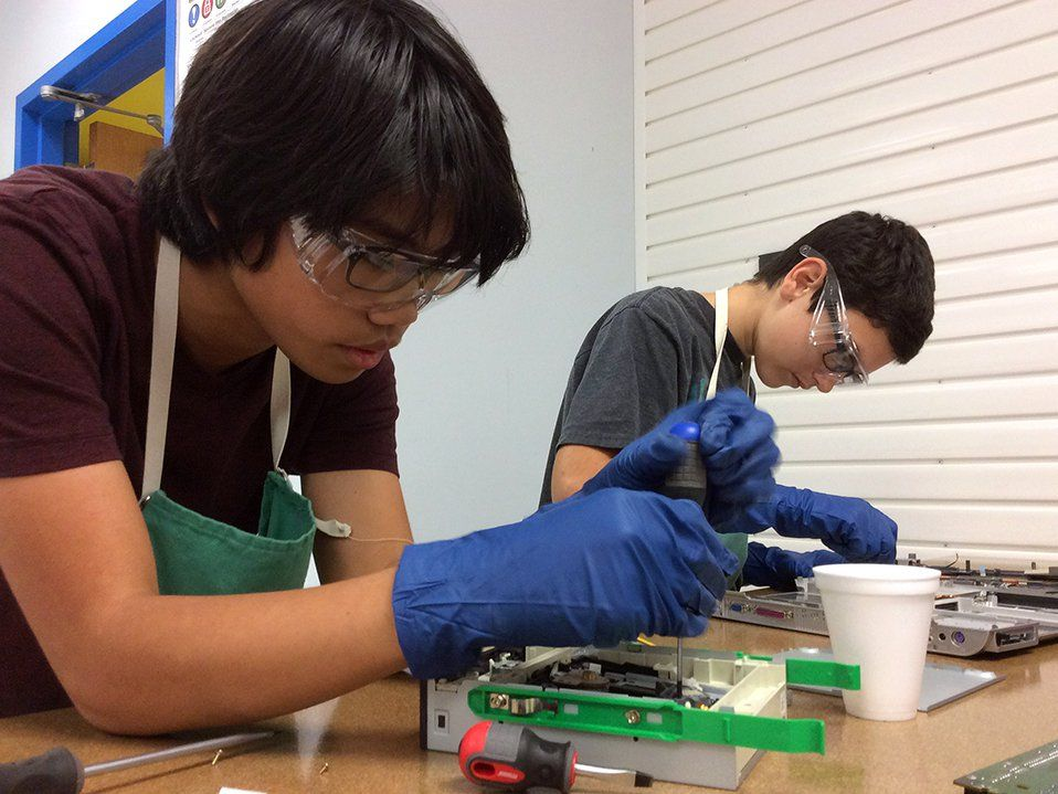 Two teenage boys in protective goggles, green aprons, and blue gloves are hovering over a desk holding a screwdriver, using it with some plastic-metal device.