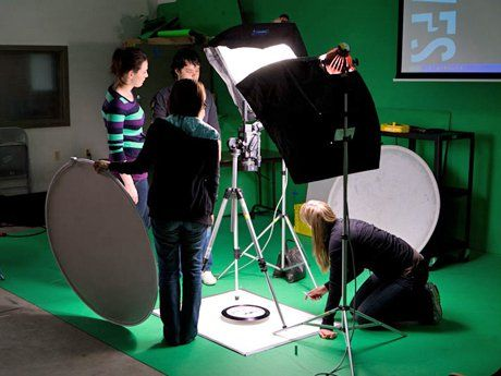 Three students and a teacher are in a green room, setting up the lighting to film.