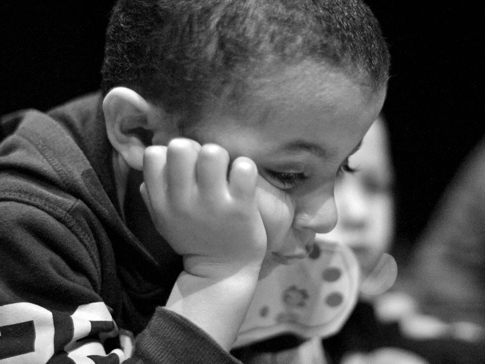 A black and white closeup of a young boy, maybe 5-years-old, in a hoodie. He's leaning forward with his head resting on his hand, and he has a solemn look on his face.