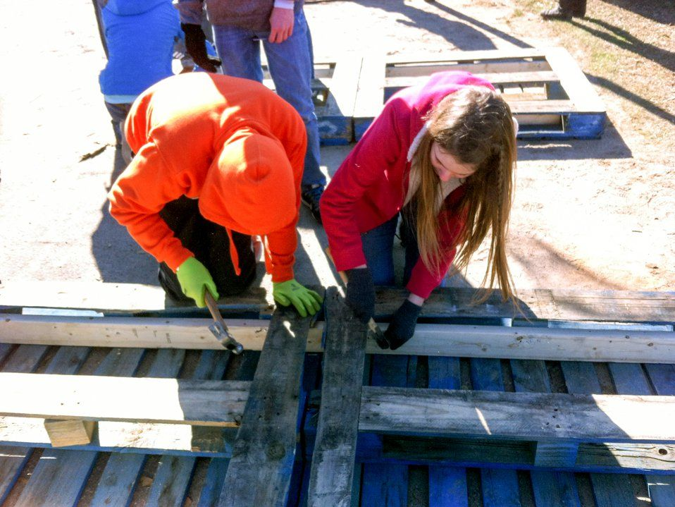 Two young students are outside, bending over planks of wood, hammering them together.