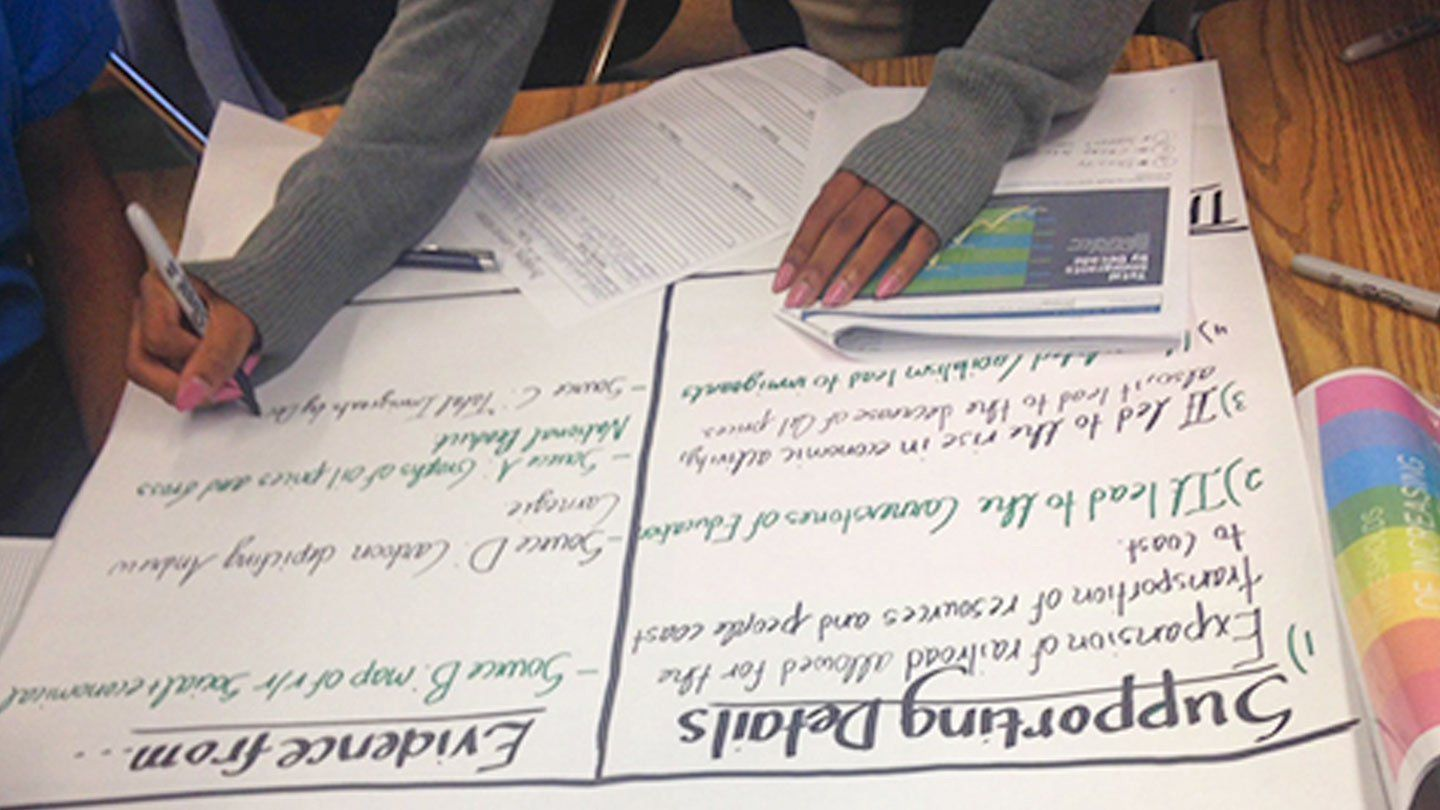 """A student is drawing on a big piece of paper, filling in two columns, """"Supporting Details"""" and """"Evidence From."""""""