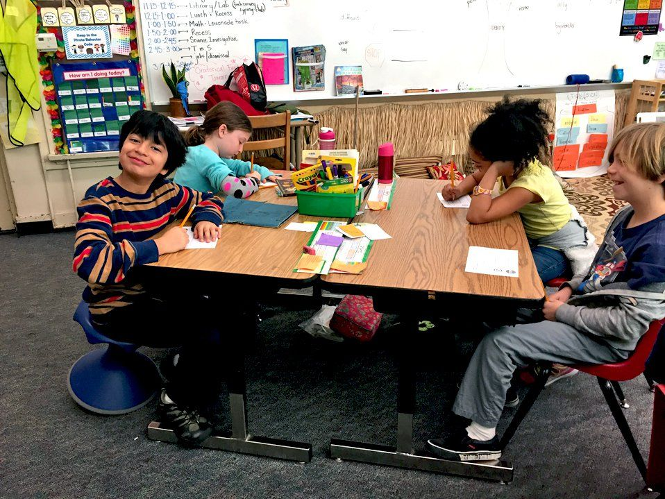 Four young students are sitting together at two, two-person desks put together as one table. They're near the front of the classroom near a whiteboard. The two girls are looking down, writing, and the two boys are looking up, smiling.