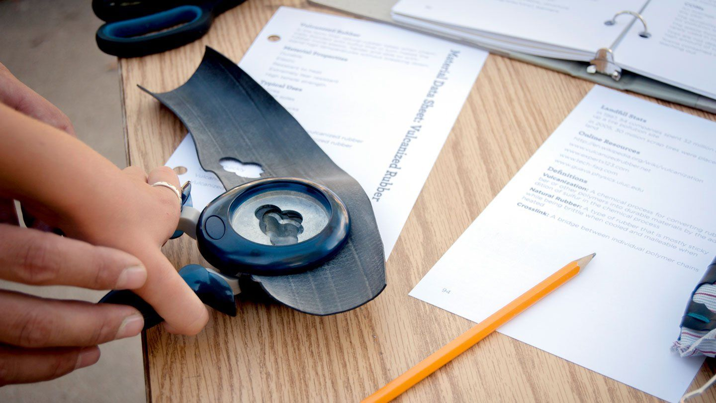 An adult's hands are guiding a student's hand to use an upscale hole punch. They're holding it on top of a desk. There's an opened binder, papers, scissors, and a pencil strewn across the desk.