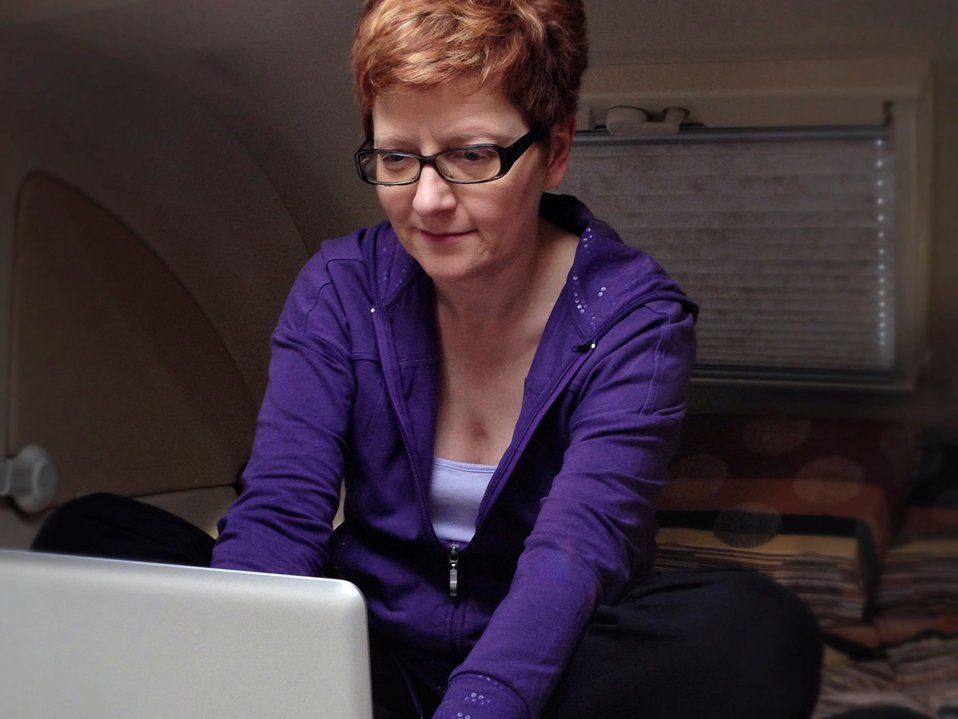 A red-headed woman in a purple sweatshirt with glasses is hunched over, sitting cross-legged, typing on her laptop.