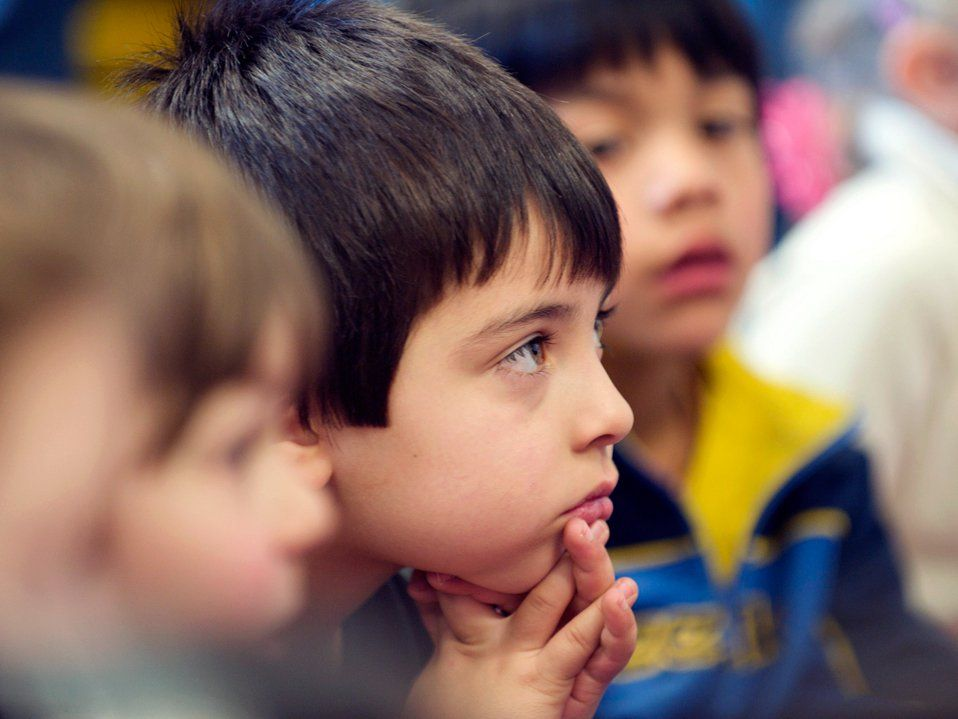 A closeup of a young boy cupping his face with his hands, sitting among other students on the floor.