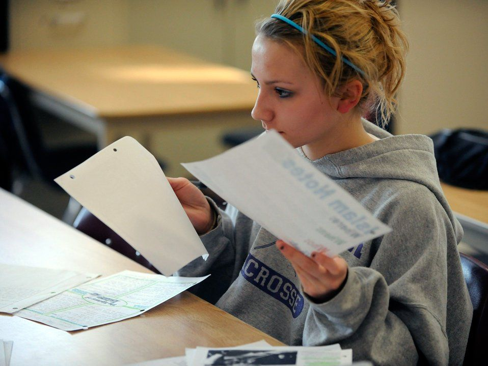 A teenage girl in a gray sweatshirt is sitting at her paper-scattered desk, holding pieces of paper in both hands.
