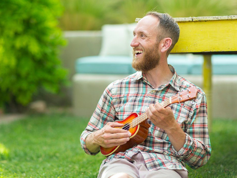 Bearded man sitting outside, smiling, playing the ukulele