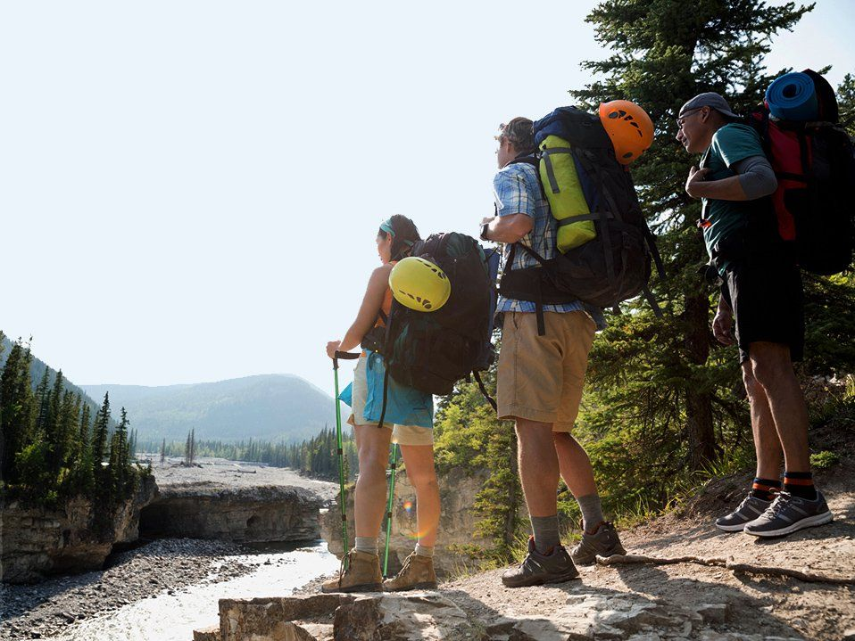 Three hikers carrying backpacks with helmets and bed rolls attached, standing looking down at a creek