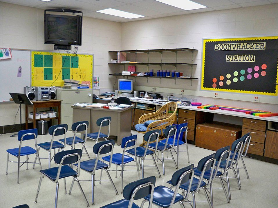 17 chairs are lined side-by-side in three rows facing the front of a classroom. At the front of the class, inches from the ceiling, a flat screen TV is attached to the wall. A countertop with drawers extends along the right side of the room.