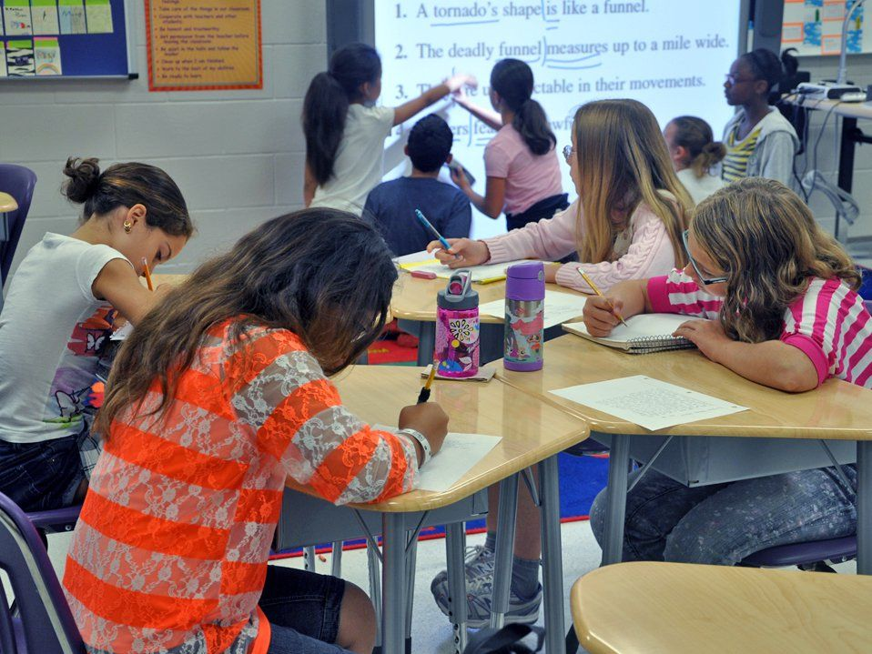 Four young girls are sitting, writing at their desks. Five young students are standing by a projector at the front of the class, pointing at the screen, which is projecting four different sentences marked with blue marker.