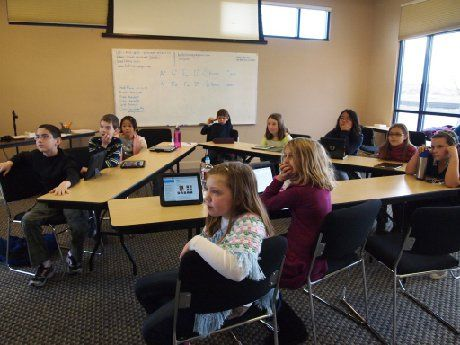 Ten students are sitting in a classroom at rectangular tables positioned in a triangle, all looking up in the same direction.
