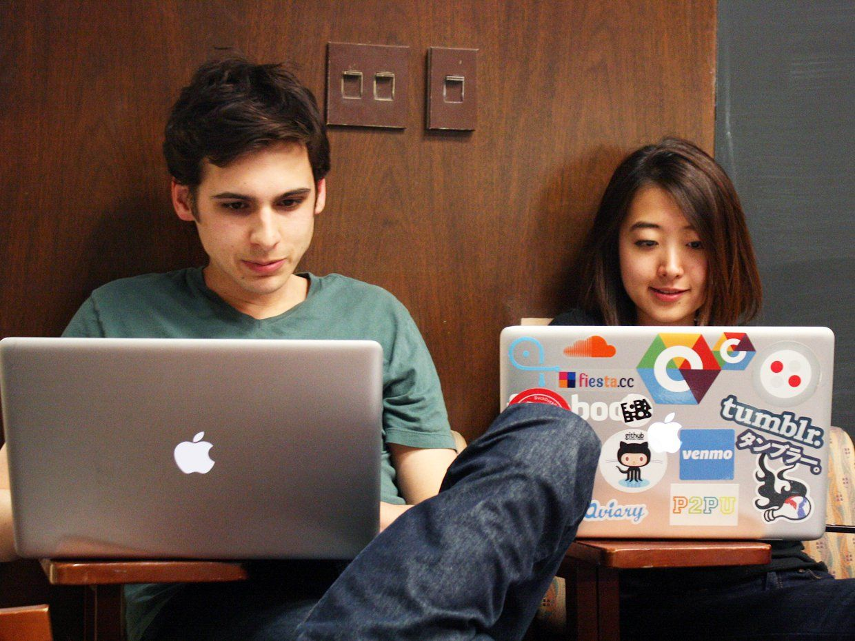 A teenage boy and girl are sitting next to each other in chairs with cloth backings and a partial desk about three times the size of an arm chair. Their chairs are up against wood-paneled walls.