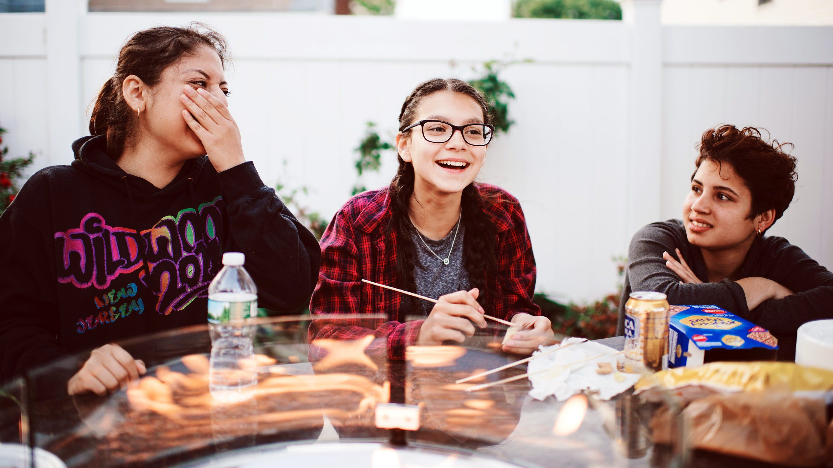 Two teenage girls are sitting outside at a glass table, eating lunch and laughing.