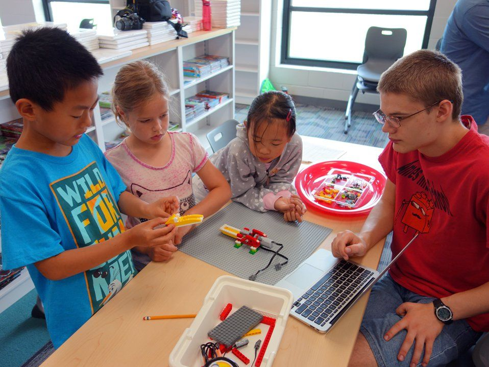 Four young students are sitting around a classroom table building a contraption out of legos and wires. It looks like it might be able to move prompted by technology.
