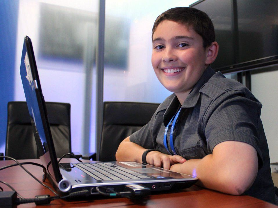A young boy is sitting at a desk with a laptop in front of him. He is smiling directly at the camera. A TV is on the wall behind him, and two leather chairs are to the right of him against a clear wall, adjacent to a similar room with a TV on the wall.