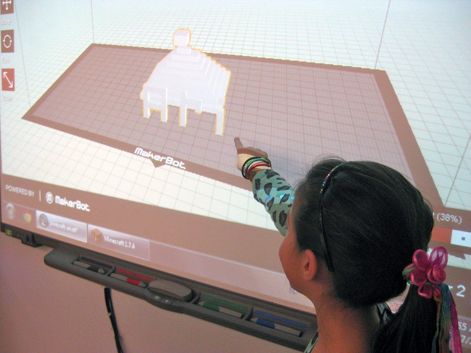 A closeup of a young girl standing next to and pointing at a projector screen. A 3D drawing made up of small squares is projected on the screen, showing the inside of a white room with a brown floor and a small white pyramid in the middle.