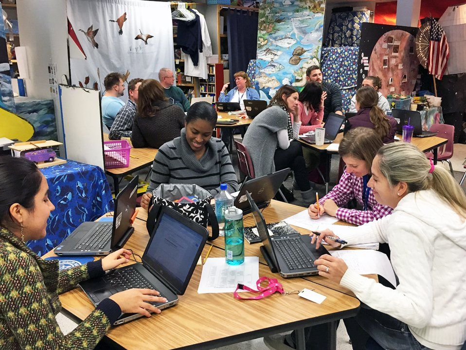 Three groups of four to five teachers are sitting at tables in a classroom talking to each other, looking at their laptops, and writing on paper.