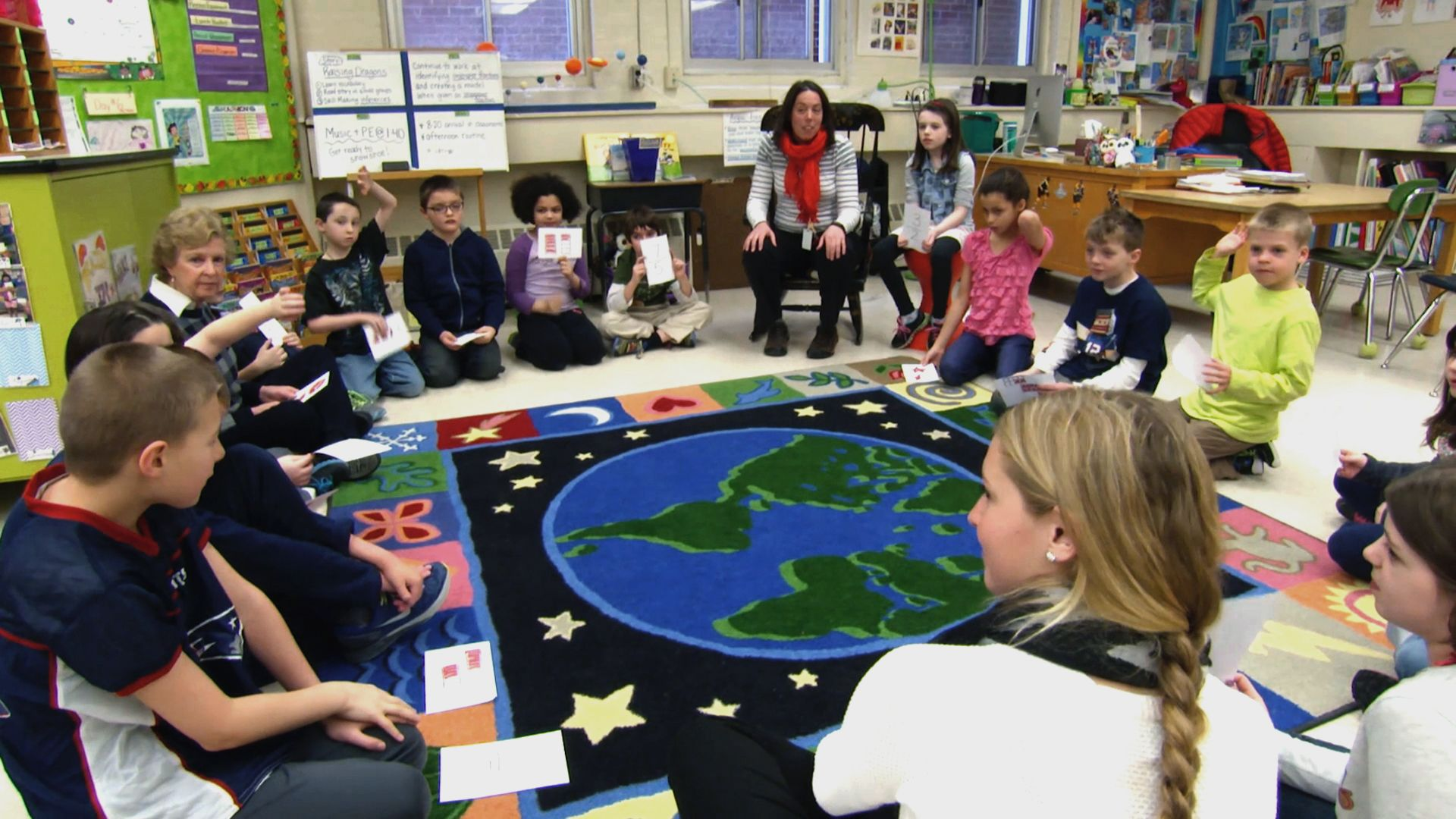 Students and teachers sitting on the classroom floor talking to each other.