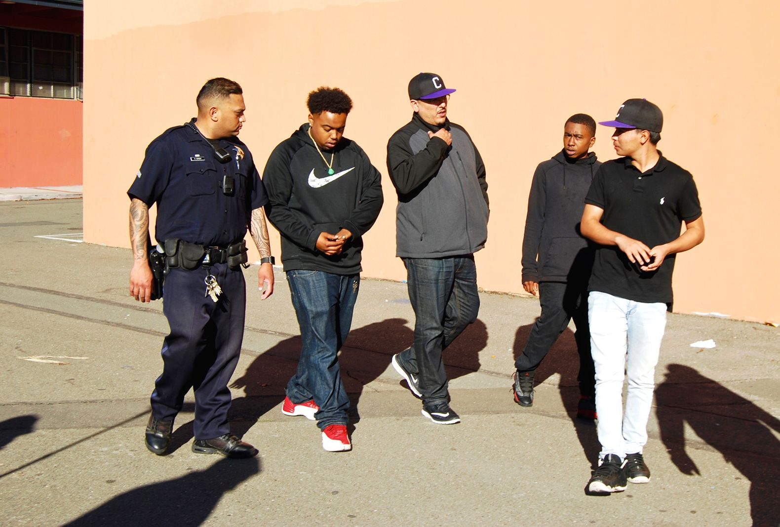 A group of Castlemont students walk with Navarro and Singh on campus.