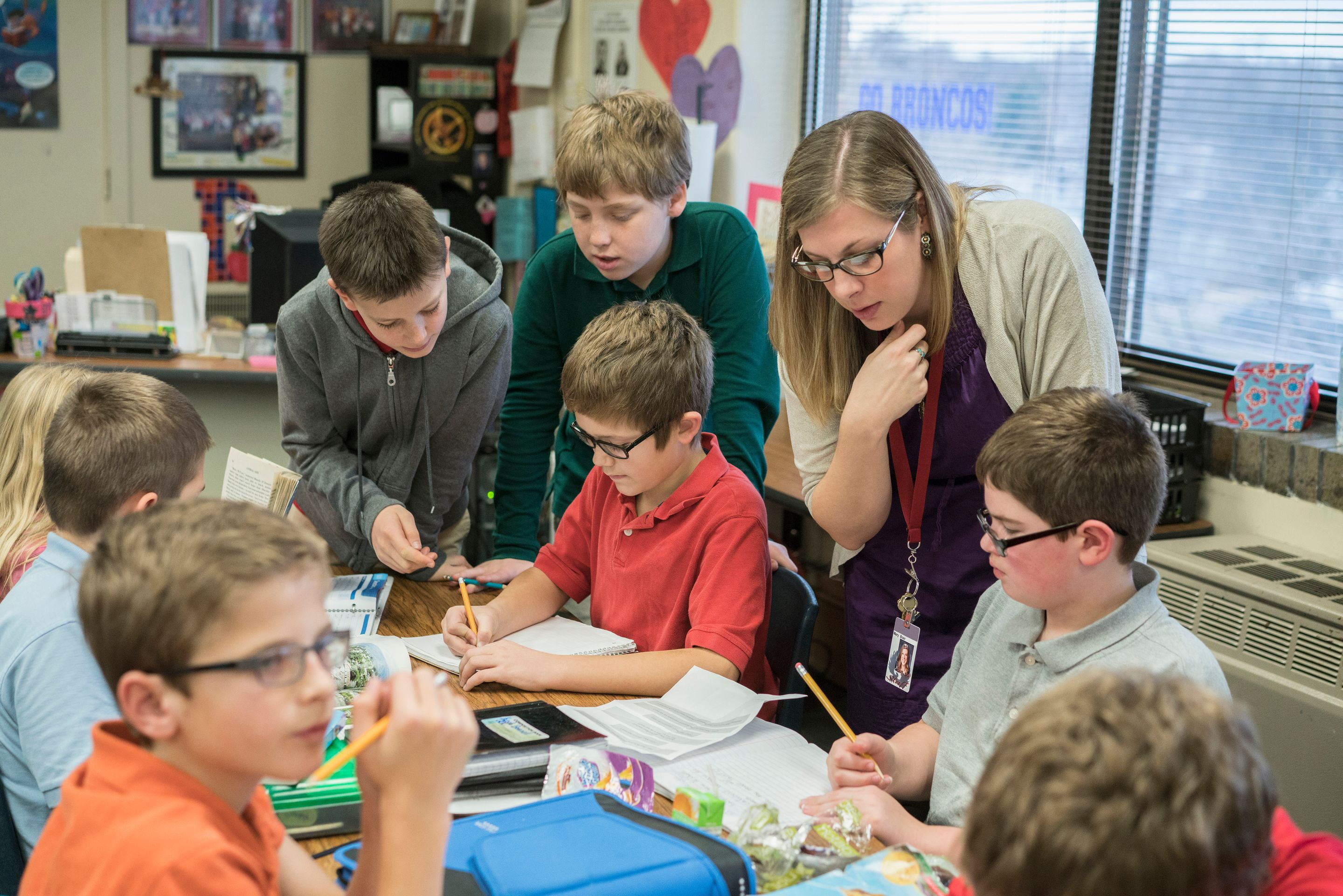 Teacher helping a group of elementary students in the classroom.