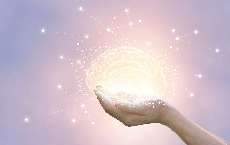 Hands holding illuminated illustration of a brain