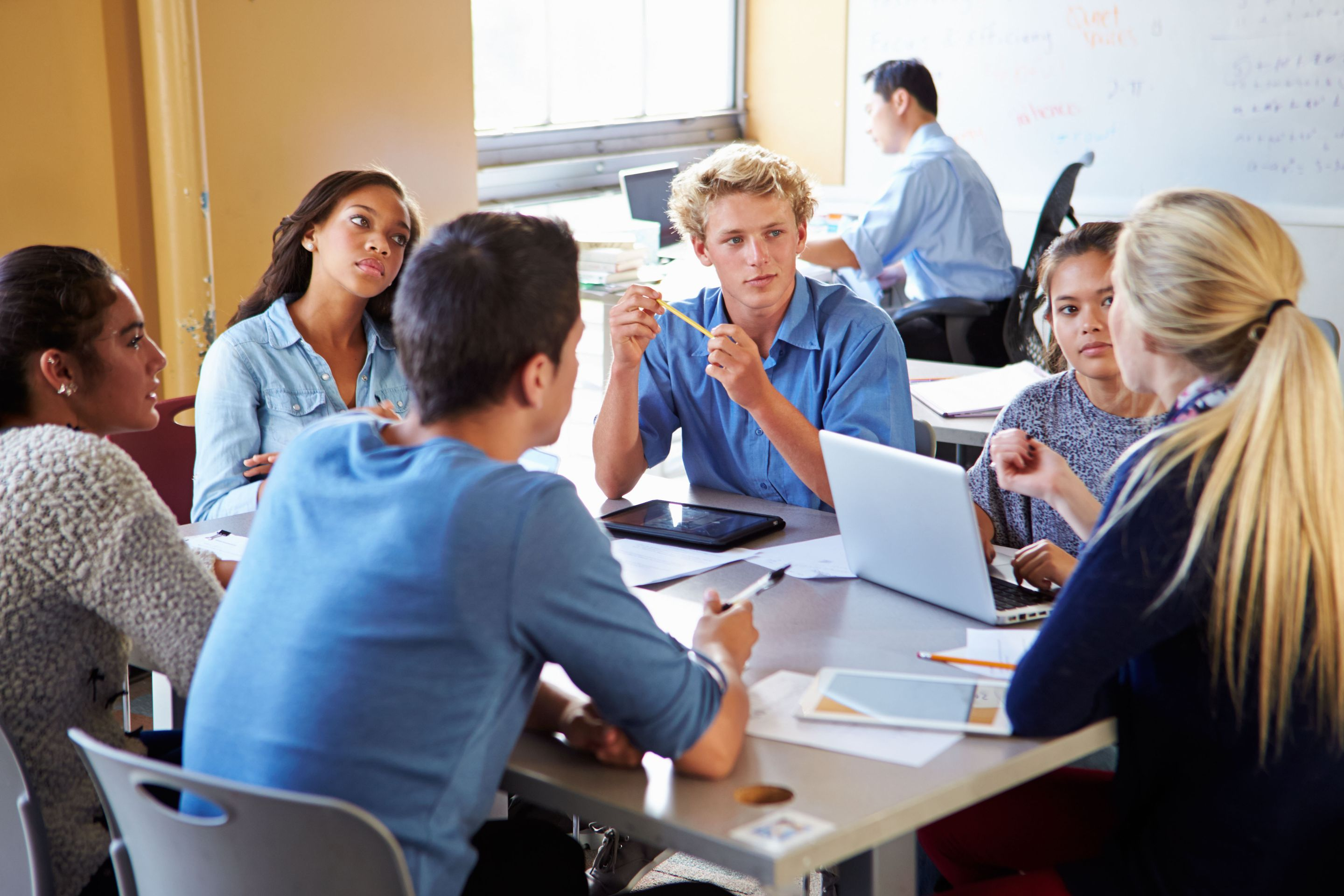 High school students discussing advertisements in a group in the classroom