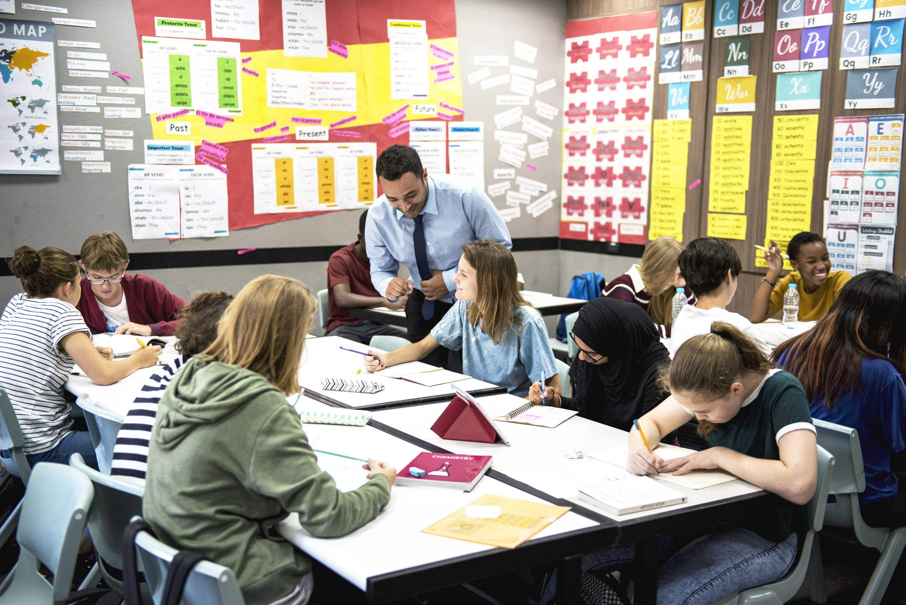 Teacher engaging with a group of high school students in the classroom.