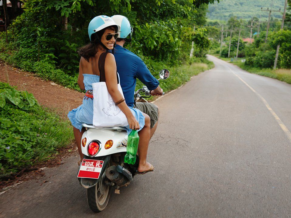 A man and woman on a motorcycle are driving on a road with tropical trees surrounding them on both sides.