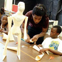 The arts are key to the Behrman experience: Haitian artist Vidho Lorville offers instruction to students in art class.