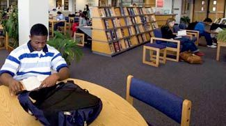 Group Effort: Senior Michael Kyem, who emigrated from Ghana, is among many students who visit JEB Stuart High School's library, which was expanded in 2002.