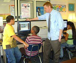 Share to Learn:  Teacher George Mayo helps students Fernando, Binyam, and Johana edit their blog posts before publishing them. In their blogs, the students record podcasts and write about a novel they read.